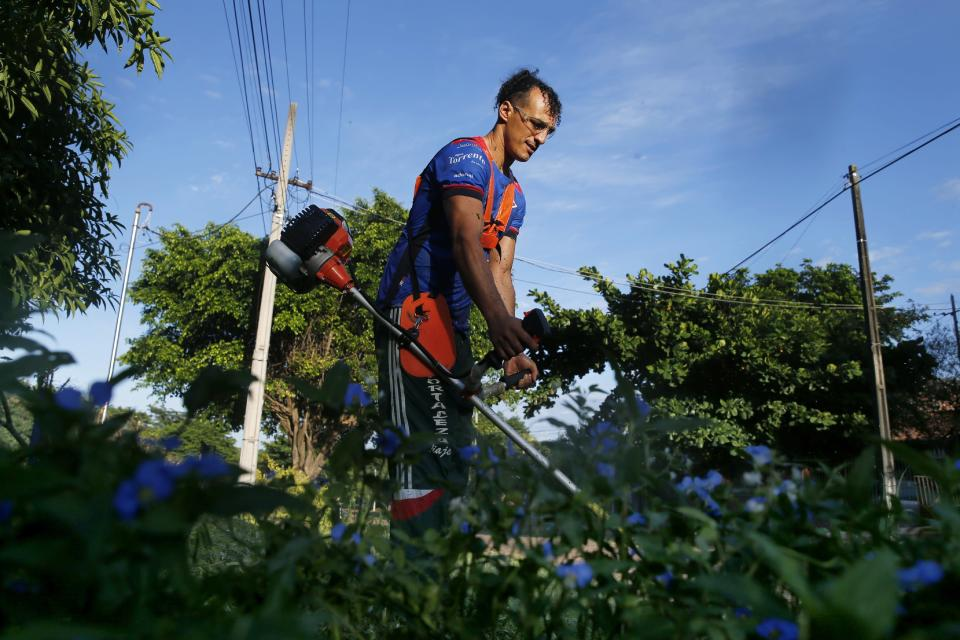"""Defender Jose """"Ruli"""" Rios, of the Fulgencio Yegros Club, second division, cuts grass in his neighborhood in Ypane, Paraguay, Saturday, Jan. 30, 2021. A professional since age 18, the 35-year-old defender helped four clubs reach Paraguay's first division. To survive during during the COVID-19 pandemic, Rios is working as a gardener as he waits for the 2021 season to begin. (AP Photo/Jorge Saenz)"""