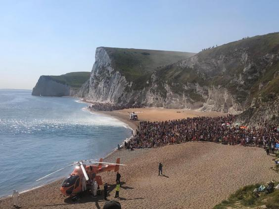 An air ambulance lands on the beach at Durdle Door as the is evacuated (PA)