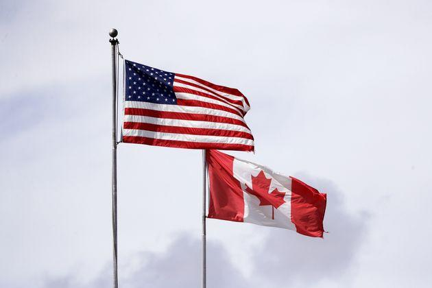 U.S. and Canadian flags fly atop the Peace Arch at the Canada-U.S. border on May 17, 2020.