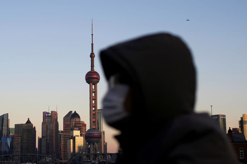 A man wearing a face mask rides a bicycle on a bridge in front of the financial district of Pudong in Shanghai