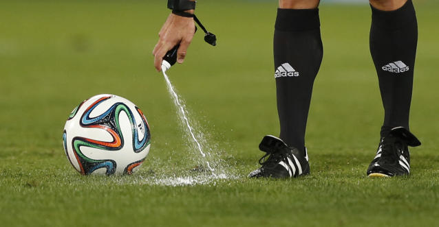 FILE - In this Wednesday, Dec. 18, 2013, file photo, referee Carlos Velasco of Spain marks a line with vanishing spray during the semi final soccer match between Raja Casablanca and Atletico Mineiro at the Club World Cup soccer tournament in Marrakech, Morocco. For the first time at a World Cup, technology will be used to determine whether a ball crosses the goal line during matches at the upcoming tournament in Brazil. With vanishing spray also being used to prevent encroachment by defenders making up a wall during free kicks, officials at the highest level of the world's most popular sport are finally getting some assistance. (AP Photo/Matthias Schrader, File)