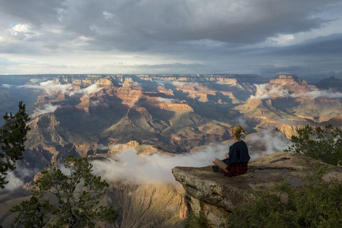 <p>A woman sits on a rock near Yavapai Point overlooking the South Rim of the Grand Canyon in Arizona. // August 7, 2015</p>