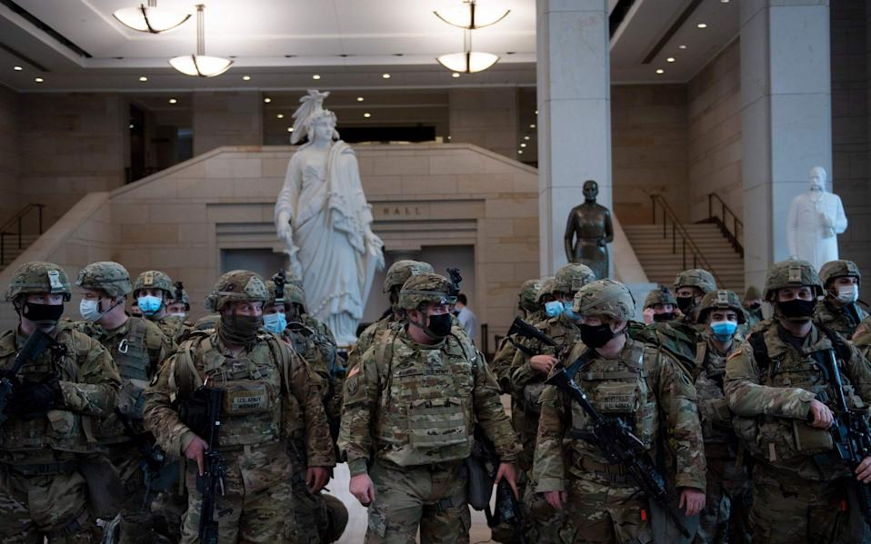 Members of the National Guard prepare in the Capitol Visitors Center on Capitol Hill in Washington, DC, January 13, 2021, ahead of an expected House vote impeaching US President Donald Trump. - The Democrat-controlled US House of Representatives on Wednesday opened debate on a historic second impeachment of President Donald Trump over his supporters' attack of the Capitol that left five dead.Lawmakers in the lower chamber are expected to vote for impeachment around 3:00 pm (2000 GMT) -- marking the formal opening of proceedings against Trump. - BRENDAN SMIALOWSKI/AFP via Getty Images