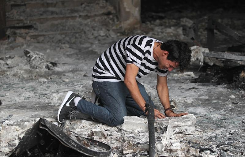 An Iraqi man reacts as he enters a building that was destroyed in a suicide-bombing attack in Baghdad's Karrada neighbourhood