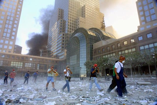 <p>People evacuate the area surrounding the World Trade Center after it was hit by two planes on Sept. 11, 2001. (Photo: Mario Tama/Getty Images) </p>