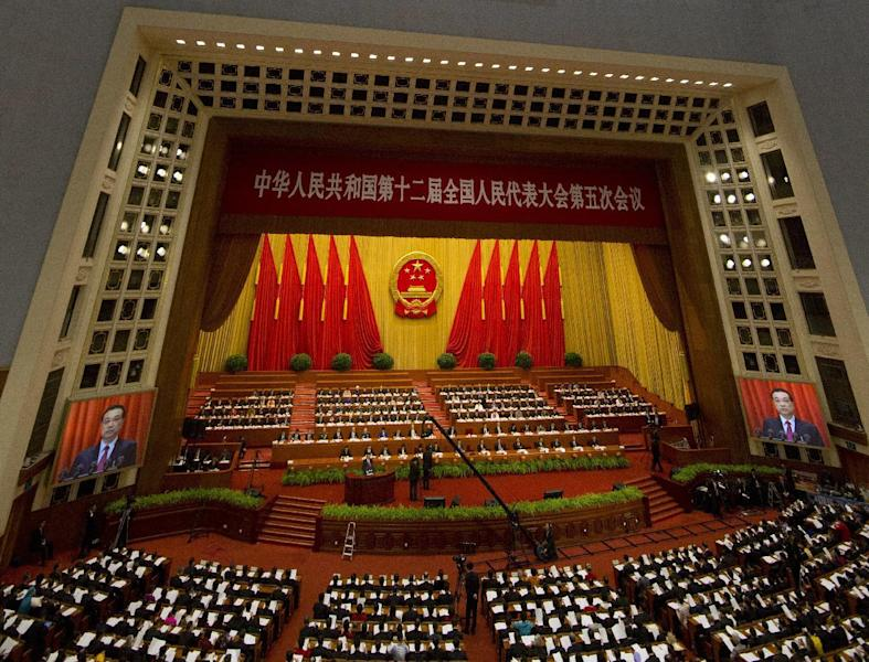 Chinese Premier Li Keqiang is displayed on screens as he delivers a work report at the opening session of the annual National People's Congress at Beijing's Great Hall of the People, Sunday, March 5, 2017. China's top leadership as well as thousands of delegates from around the country are gathered at the Chinese capital for the annual legislature meetings. (AP Photo/Ng Han Guan)