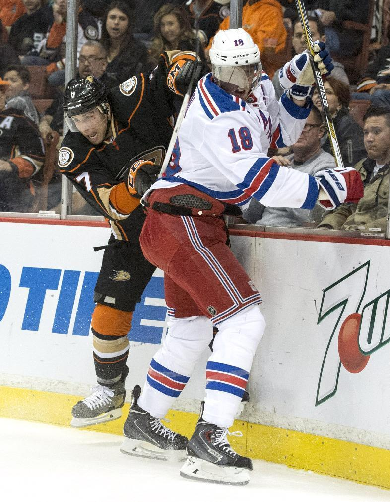 The Ducks' Andrew Cogliano, left, body checks the Rangers' Marc Staal during a game in Los Angeles on Wednesday night Jan. 7, 2014. (AP Photo/The Orange County Register, Kyusung Gong)