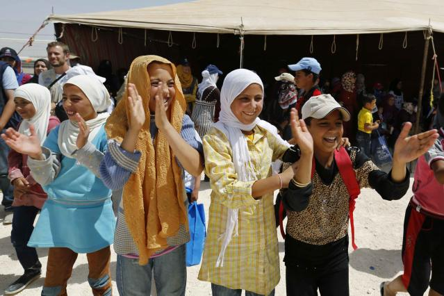 Syrian refugee girls applaud as they watch the final soccer match in a tournament of their own at Al Zaatri refugee camp in the Jordanian city of Mafraq, near the border with Syria, June 20, 2014. As soccer teams from around the world gather for this year's World Cup in Brazil, Syrian refugees in Jordan are taking part in a soccer tournament of their own to mark World Refugee Day, which falls on June 20. The tournament aims to help refugees to respond to the challenges posed by their displacement, and the impact of the conflict in Syria on their lives. Some 600,000 Syrian refugees currently reside in Jordan, part of a displaced population of some 2.8 million Syrians across the Middle East. REUTERS/Muhammad Hamed (JORDAN - Tags: POLITICS CIVIL UNREST SPORT SOCCER WORLD CUP SOCIETY IMMIGRATION)