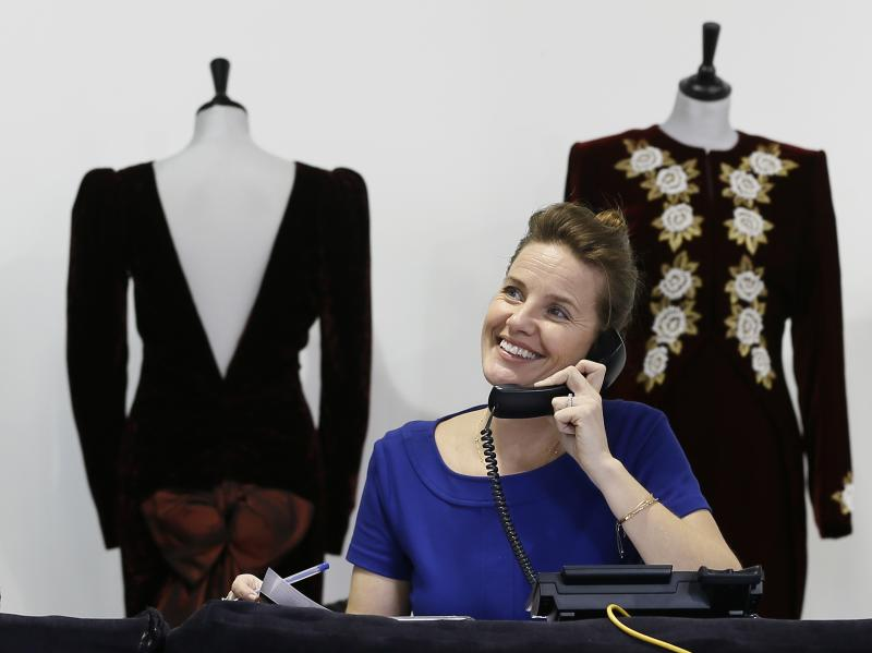 An auction house worker takes telephone bids during the Kerry Taylor 'Fit for a Princess' auction in London, Tuesday, March 19, 2013. The auction was of ten dresses formerly owned and worn by Britain's Princess Diana. The total hammer price for the ten lots was 719,000 pounds ($1.09million US) not including the 20 percent buyers premium . (AP Photo/Kirsty Wigglesworth)