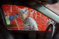 Vivas Hand Car Wash owner Telesforo Vivas, of Sanford N.C., who has been in business for 5 years, washes a car window, in Burlington, N.C., Wednesday, March 11, 2020. His car wash is along a businesses strip of Latino-owned businesses. (AP Photo/Jacquelyn Martin)
