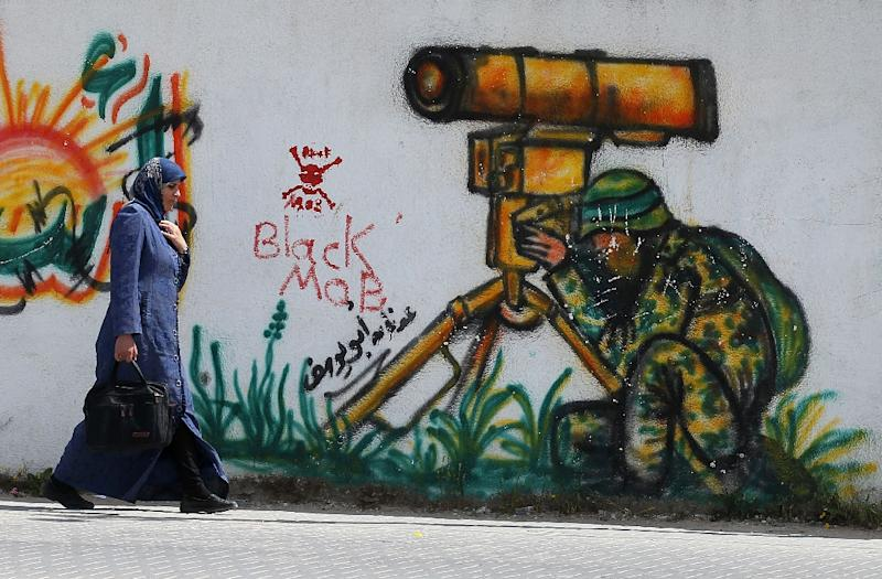 A Palestinian woman walks past a mural in the east of Khan Yunis, in the southern Gaza Strip, on March 26, 2015 (AFP Photo/Said Khatib)