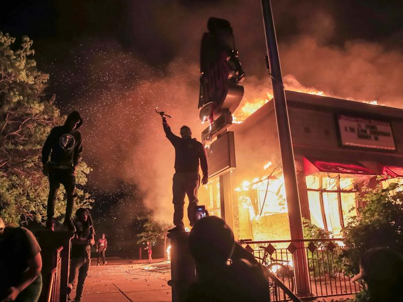 Protesters burn an Arby's fast food restaurant near the Minneapolis Police Department: EPA