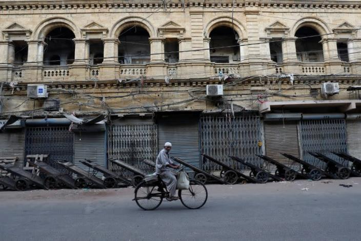 A hawker on bicycle rides past a closed wholesale cloth market during a countrywide strike in Karachi,