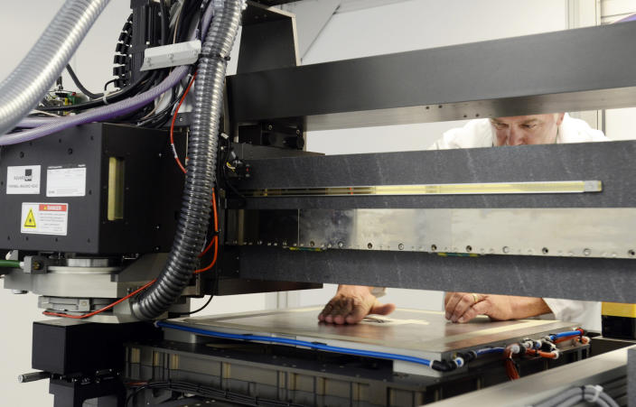 In this Aug. 28, 2013 photo, Kodak Research Technician, Larry Rowley, prepares a substrate for laser writing on a flat bed laser writer at the Kodak laser writing lab in Rochester, N.Y. Kodak scientists created printers, inks and other materials designed to improve resolution, while also increasing the variety of surfaces that can be printed on, boosting printing speed and lowering costs for customers. (AP Photos/Heather Ainsworth)