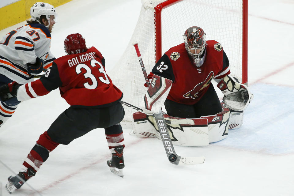 Arizona Coyotes goaltender Antti Raanta (32) makes a save on a shot by Edmonton Oilers center Connor McDavid (97) as Coyotes defenseman Alex Goligoski (33) applies pressure during the third period of an NHL hockey game Tuesday, Feb. 4, 2020, in Glendale, Ariz. The Coyotes won 3-0. (AP Photo/Ross D. Franklin)