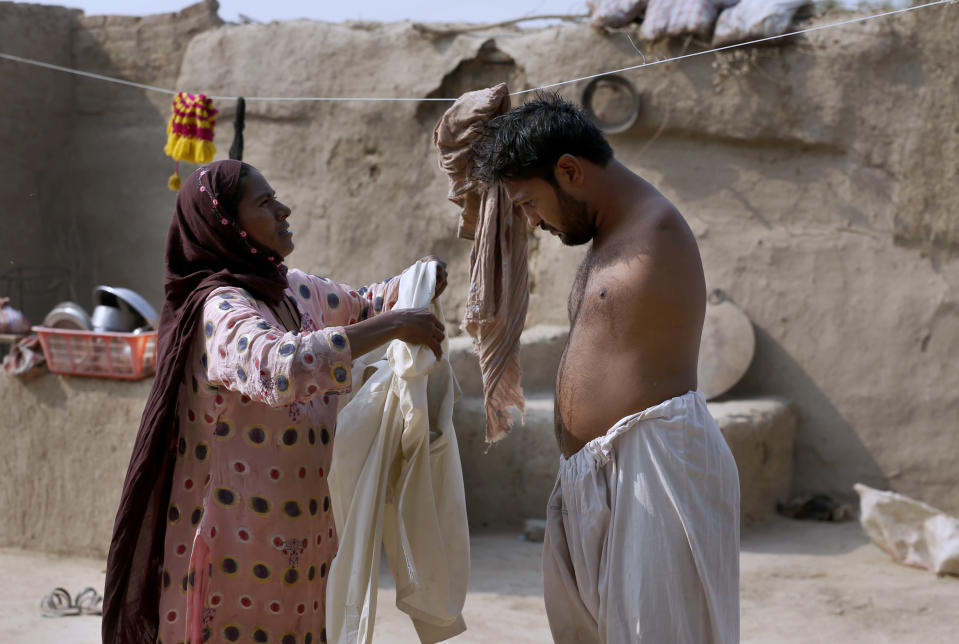 Rizia Bibi, left, helps his son Mohammad Ikram, who play snooker with his chin, to wear long shirt at their home in a village near Samundri town, Pakistan, Sunday, Oct. 25, 2020. Ikram, 32, was born without arms, but everyone simply admires his snooker skills when he hits the cue ball with his chin and pots a colored ball on a snooker table. He lives in a remote rural town of Punjab province and his physical disability doesn't come in his way to fulfill his childhood dream of playing the game of snooker. (AP Photo/Anjum Naveed)