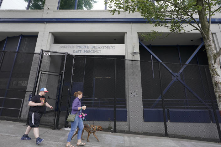 Pedestrians walk past the Seattle Police Dept. East Precinct headquarters, Saturday, July 31, 2021, in Seattle in an area that was occupied last year when demonstrators took over part of the city's Capitol Hill neighborhood. The issues of policing, equity, disorder and homelessness will be factors in Seattle's mayoral primary on Tuesday, Aug. 3. (AP Photo/Ted S. Warren)