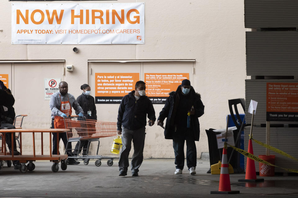 Home Depot customers carry their purchases as they leave the store, Friday, April 3, 2020 during the coronavirus pandemic in New York. (AP Photo/Mark Lennihan)