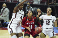 North Carolina State forward Jakia Brown-Turner (11) looks for a shot against South Carolina's Aliyah Boston (4) and Brea Beal (12) during the first half of an NCAA college basketball game Thursday, Dec. 3, 2020, in Columbia, S.C. (AP Photo/Sean Rayford)