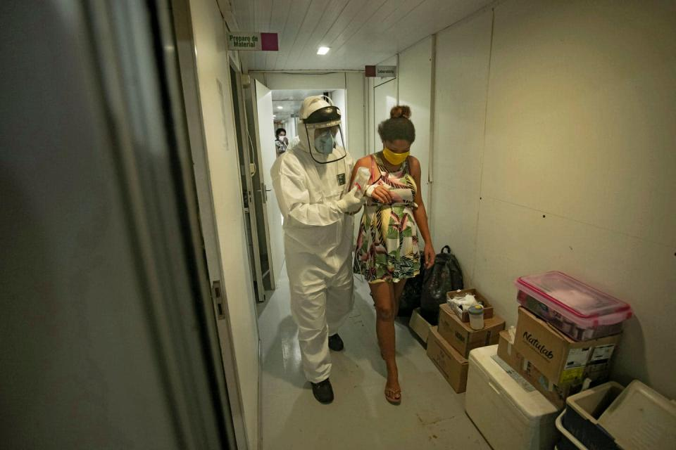 Health worker in full-body PPE walks a pregnant woman down a hall