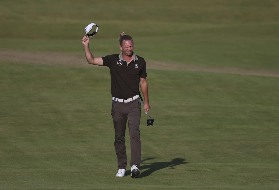 Germany's Marcel Siem acknowledges the crowd as he walks to the 18th green during the third round of the British Open Golf Championship at Royal St George's golf course Sandwich, England, Saturday, July 17, 2021. (AP Photo/Ian Walton)