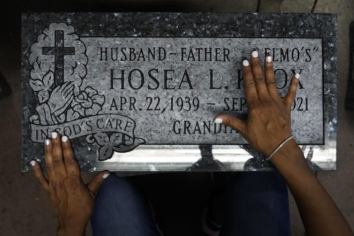 """Tara Knox Stockdale slides her hands over the tombstone Leon Brown just made for his former boss, Tara's father, Hosea Knox, Tuesday, Sept. 14, 2021, in Chicago. """"It becomes real again"""" said Stockdale about her father's recent passing. (AP Photo/Charles Rex Arbogast)"""