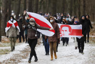 FILE In this file photo taken on Sunday, Dec. 13, 2020, Demonstrators wearing face masks to help curb the spread of the coronavirus carry old Belarusian national flags during an opposition rally to protest the official presidential election results in Minsk, Belarus. Protests against President Alexander Lukashenko that gripped Belarus for months seem quelled by Winter's cold and harsh police action, but opposition forces are preparing to turn up the heat in the spring and observers say Lukashenko doesn't have a clear strategy to overcome new unrest.(AP Photo, File)