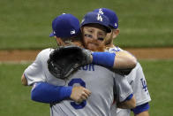 Los Angeles Dodgers' Justin Turner hugs Chris Taylor (3) after Game 2 of the National League Championship Series baseball game against the Milwaukee Brewers Saturday, Oct. 13, 2018, in Milwaukee. The Dodgers won 4-3. (AP Photo/Charlie Riedel)