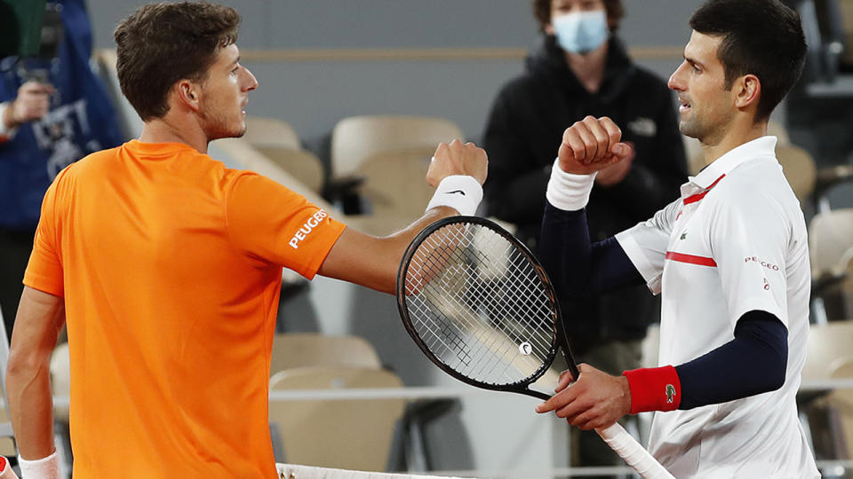 Novak Djokovic meets Pablo Carreno Busta at the net following victory in their Men's Singles quarterfinals match at the French Open. (Photo by Clive Brunskill/Getty Images)