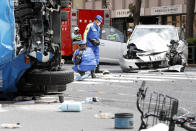 FILE - In this April 19, 2019, file photo, police officers inspect the scene of a car accident in Tokyo. The Tokyo District Court on Thursday, Sept. 2, 2021, sentenced Kozo Iizuka, a 90-year-old former top bureaucrat, to five years in prison in the fatal car accident on a busy Tokyo street, killing a 3-year-old girl and her mother in a high-profile case in a fast-aging country where elderly driving has become a major safety concern. (Shinji Kita/Kyodo News via AP, File)
