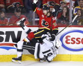 Los Angeles Kings' Alex Iaffalo, bottom, takes a hit from Calgary Flames' Elias Lindholm, of Sweden, during the third period of an NHL hockey game Saturday, Dec. 7, 2019, in Calgary, Alberta. (Larry MacDougal/The Canadian Press via AP)
