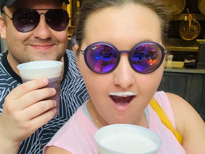Carly Caramanna and her husband drinking butterbeer at universal studios orlando