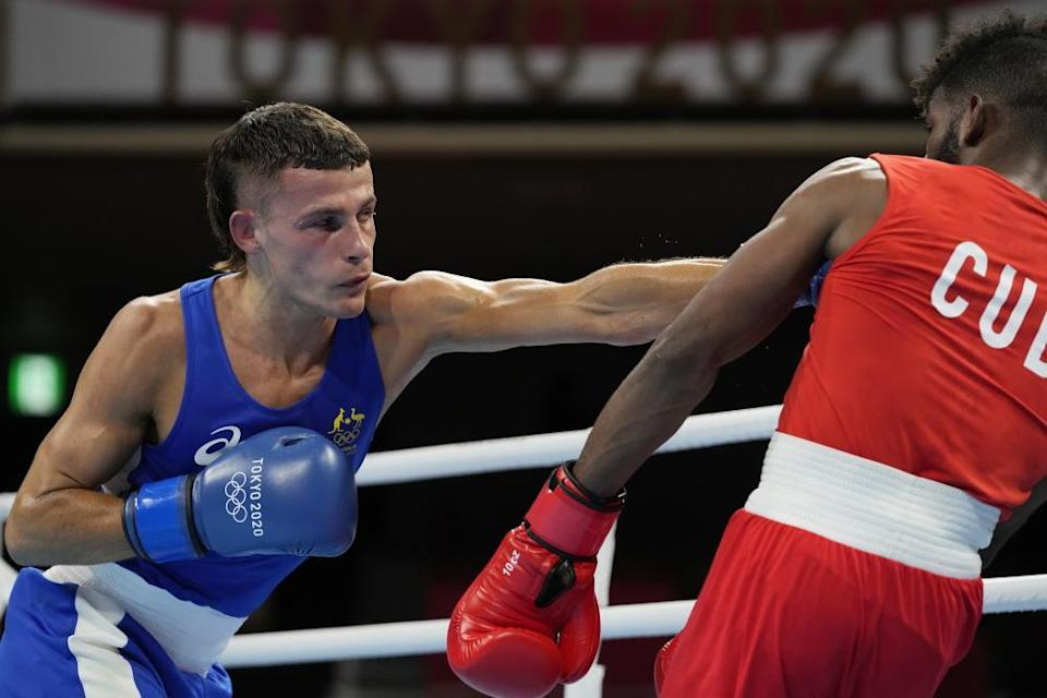 Cuba's Andy Cruz, right, exchanges punches with Australia's Harry Garside.