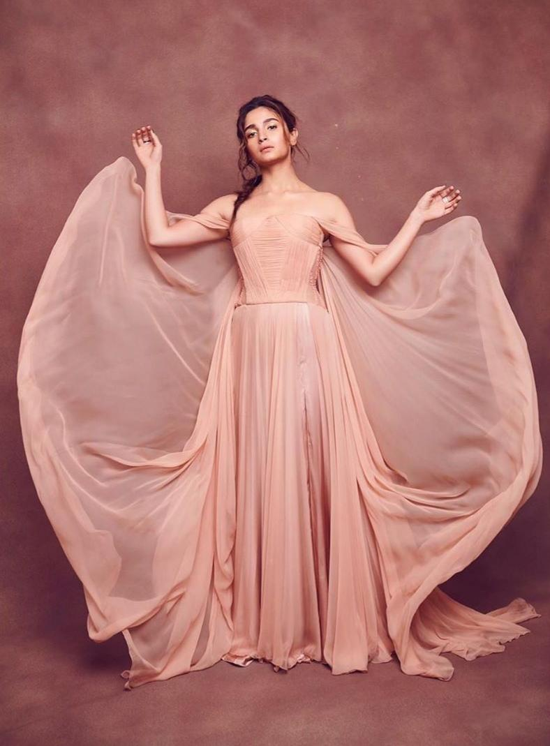 Let's start by giving credit to Georges Chakra for this ethereal ball gown. In this flowy off-shoulder number, featuring a statement bow at the back, the 'Gully Boy' star rose from being dramatic and romantic and transformed into a sequence from a Disney fairy tale walking the green IIFA carpet. A messy side-braid, and bronze make-up accentuated her naturally chiseled yet cherubic features. We can't get over how the color of the attire matched perfectly with the actress's skin, making the outfit look like an extension of herself.