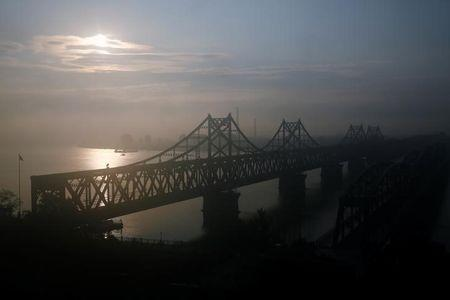The sun rises behind the bridge over Yalu River that connects China's Dandong, Liaoning province, and North Korea's Sinuiju, September 11, 2016. REUTERS/Thomas Peter