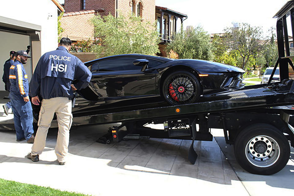 This photo provided by U.S. Immigration and Customs Enforcement shows special agents with HSI Los Angeles's El Camino Real Financial Crimes Task Force seize a Lamborghini from an Orange County businessman on Thursday, April 6, 2021, in Irvine, Calif. Mustafa Qadiri, 38, of Irvine, was named in a federal grand jury indictment and has pleaded not guilty to charges he obtained $5 million in federal coronavirus-relief loans for phony businesses and then used the money for lavish vacations and to buy a Ferrari, Bentley and Lamborghini, prosecutors said Monday, May 10. (U.S. Immigration and Customs Enforcement via AP)