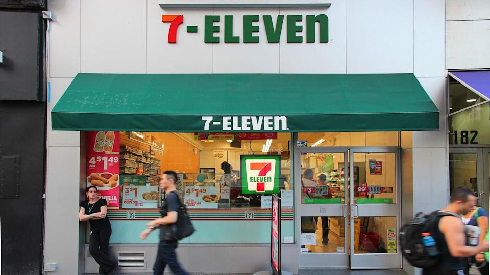 NEW YORK, USA - JULY 3, 2013: People walk past 7-Eleven convenience store in New York.