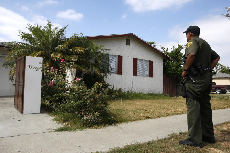 Orange County sheriff's deputy Dan Mendoza views a foreclosed home which he has to enforce an eviction order on, in Fullerton, California, June 23, 2009. REUTERS/Lucy Nicholson (UNITED STATES SOCIETY BUSINESS)