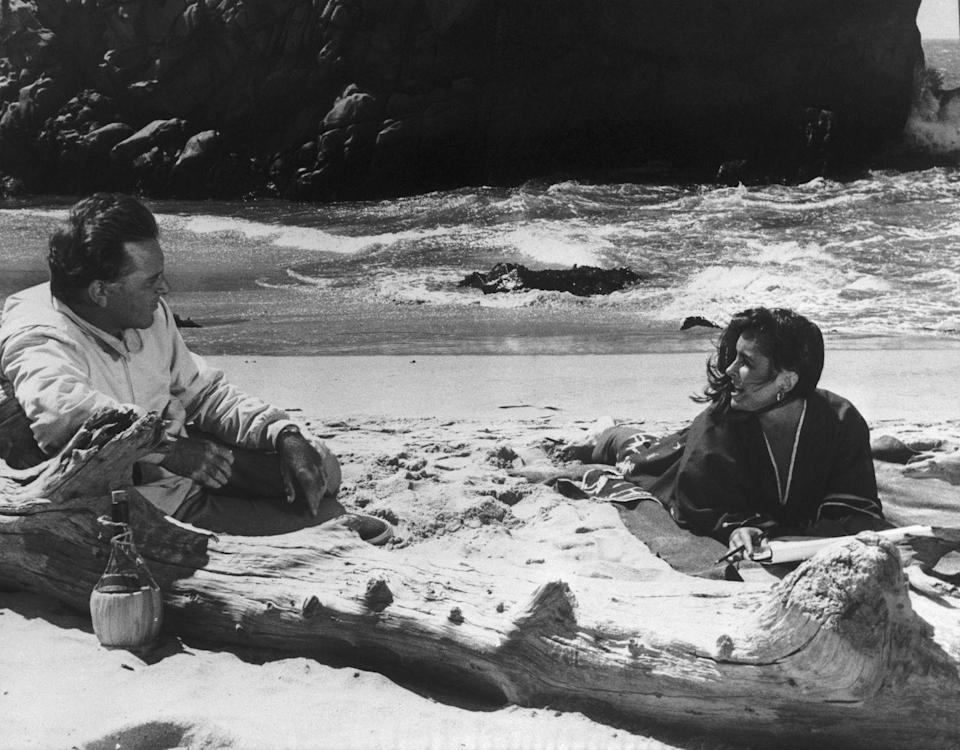 <p>Elizabeth Taylor and husband Richard Burton relax in the sand while they film <em>The Sandpiper</em> in 1965.</p>