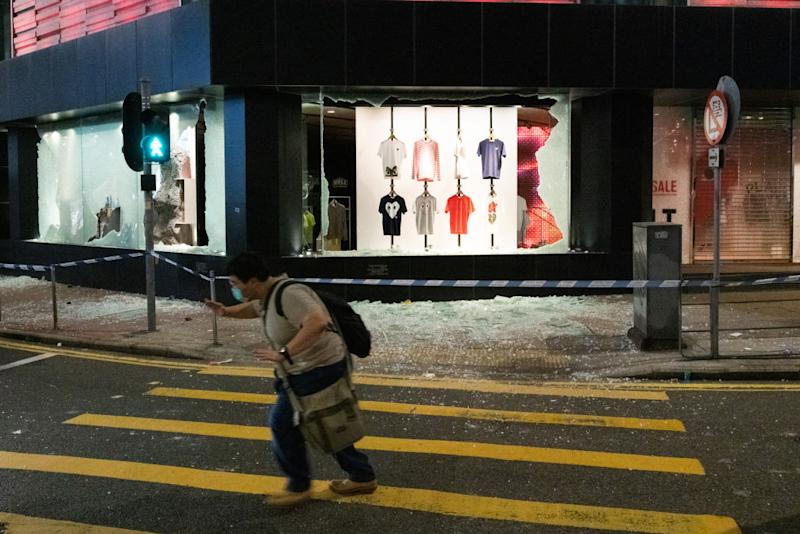 A man cautiously walks past a vandalised clothing shop during the anti-government rally. Source: Getty