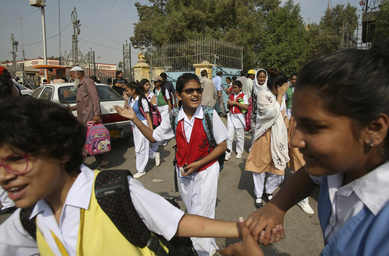 Girls leave their school in Karachi, Pakistan, Tuesday, Nov. 13, 2018. Human Rights Watch released a 111-page report Tuesday, that said millions of girls in Pakistan are still out of school, mostly because the government spends less money on education. The international rights group said they are deprived of an education for multiple reasons, including a shortage of government schools. (AP Photo/Fareed Khan)