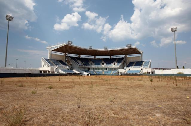FILE - In this Thursday, Aug. 2, 2012, file photo, weeds sprout in the remains of what was once the playing field at the abandoned Olympic softball venue in southern Athens. The legacy of Athens' Olympics has stirred vigorous debate, and Greek authorities have been widely criticized for not having a post-Games plan for the infrastructure. While some of the venues built specifically for the games have been converted for other uses, many are underused or abandoned, and very few provide the state with any revenue. Some critics even say that the multibillion dollar cost of the games played a modest role in the nation's 2008 economic meltdown. (AP Photo/Thanassis Stavrakis)