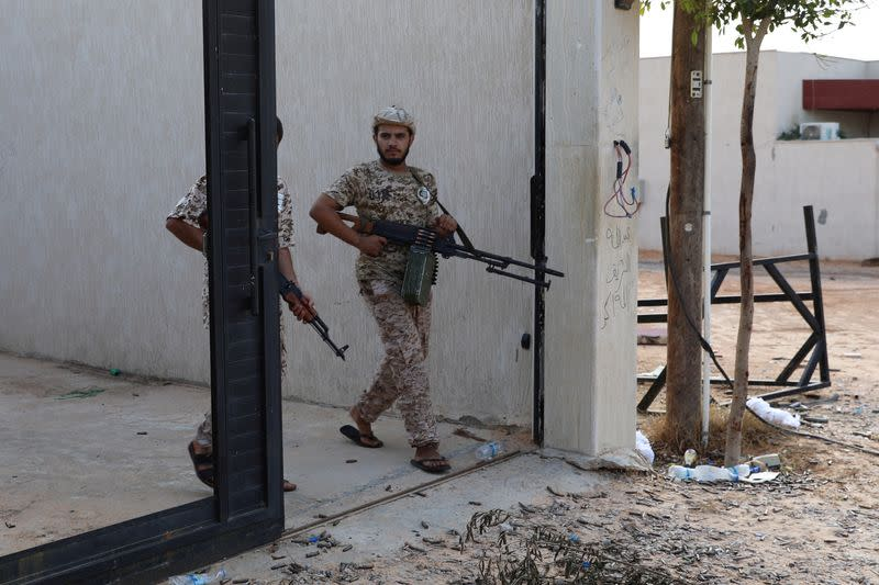 FILE PHOTO: Members of the Libyan internationally recognized government forces carry weapons in Ain Zara, Tripoli