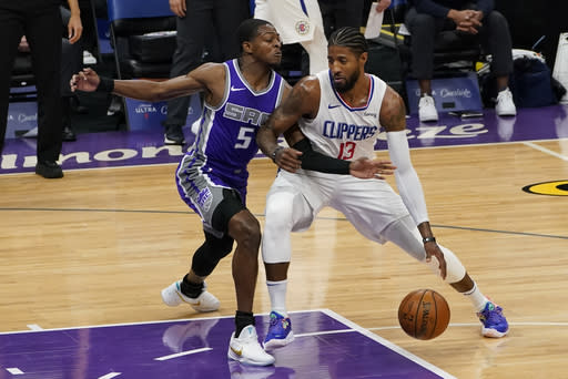Los Angeles Clippers guard Paul George, right, drives to the basket against Sacramento Kings guard De'Aaron Fox during the first quarter of an NBA basketball game in Sacramento, Calif., Friday, Jan. 15, 2021. (AP Photo/Rich Pedroncelli)