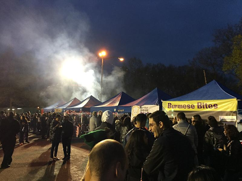 This April 22, 2017 photo shows the Queens Night Market in New York City's Corona, Queens, neighborhood, with people waiting on line at Burmese Bites and other food vendor tents. The market showcases about 50 food vendors, many of them immigrants selling examples of cuisine from their home countries, and is modeled on traditional night markets found in Asia. Similar night markets are popping up in other cities around the U.S. (AP Photo/Beth J. Harpaz)