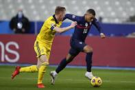 France's Kylian Mbappe, right, controls the ball as Sweden's Emil Krafth defends during the UEFA Nations League soccer match between France and Sweden at the Stade de France stadium in Saint-Denis, northern Paris, Tuesday, Nov. 17, 2020. (AP Photo/Francois Mori)