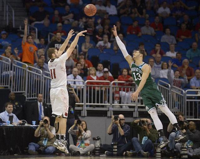 Louisville forward Luke Hancock (11) takes a 3-point shot as Manhattan forward Emmy Andujar (13) defends during the second half of a second-round game in the NCAA college basketball tournament Thursday, March 20, 2014, in Orlando, Fla. Louisville defeated Manhattan 71-64. (AP Photo/Phelan M. Ebenhack)