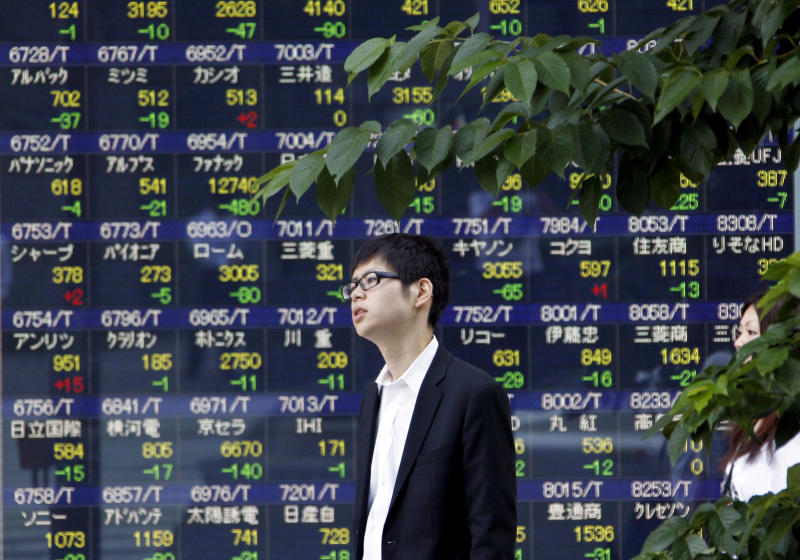 A man stands in front of the stock price display of a securities firm in Tokyo Monday, July 9, 2012. Asian stocks were lower Monday after a disappointing U.S. jobs report stoked concern that the world's biggest economy remains mired in weak growth. (AP Photo/Koji Sasahara)