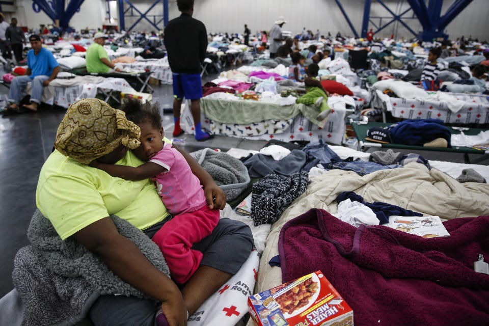 Quinisha Runnels holds her cousin, Mimi Runnels, 2, on a cot at the George R. Brown Convention Center where nearly 10,000 people are taking shelter. (AP)