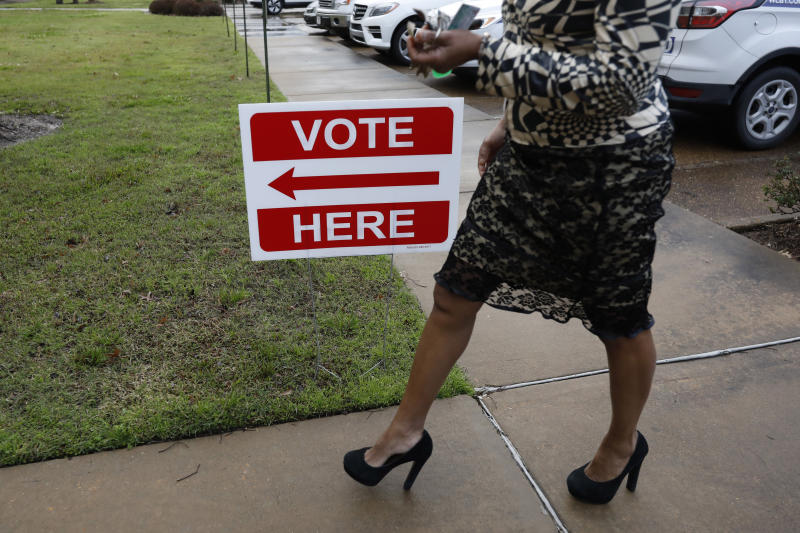 A voter rushes to the polls in Ridgeland, Miss., Tuesday, March 10, 2020, as people participate in the Republican and Democratic party primaries statewide. (AP Photo/Rogelio V. Solis)
